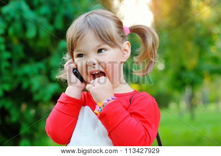 Little Girl Shouting Into The Phone In A Park