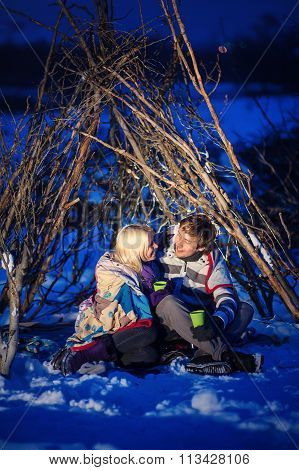 couple embracing sitting on the snow at night