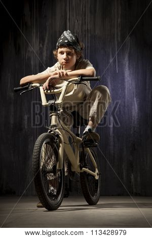 teenager on a bicycle on a background of industrial landscape