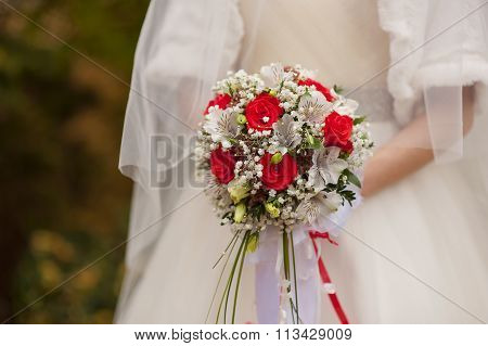 Bridal Bouquet Of Red Roses In Bride's Hands