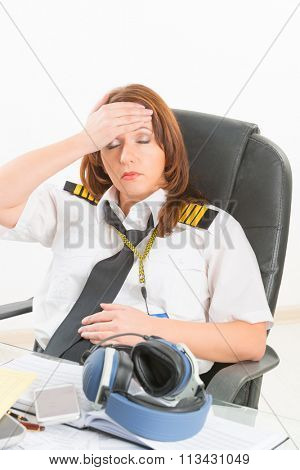 Overworked tired woman pilot wearing uniform with epaulettes resting or sleeping in briefing room