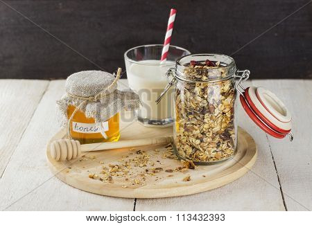 Granola In Glass Jar, Glass Of Milk And Jar Of Honey On White Wooden Table