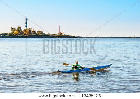 Man makes a trip by canoe on river Daugava near port of Riga