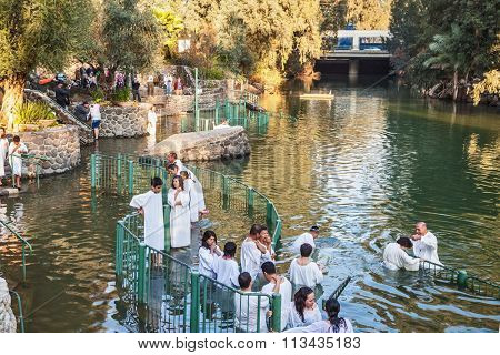 YARDENIT, ISRAEL - JANUARY 21, 2012: Christian pilgrims baptized in the Jordan River. They enter the water, dressed in special white shirt