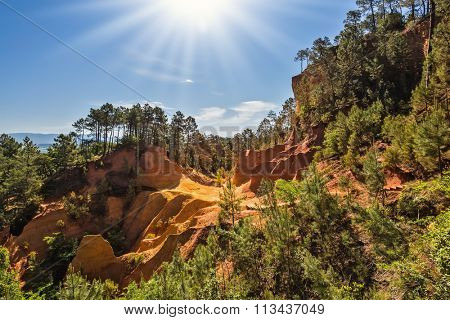 Roussillon, Provence Red Village. Green trees create contrast with the ocher. Multi-colored ocher outcrops - from yellow to orange-red