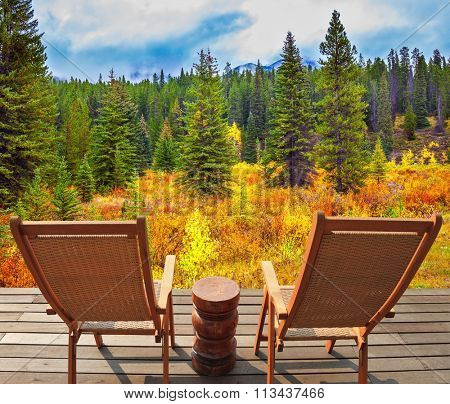 The lush colorful golden autumn in the Rocky Mountains of Canada. On the wooden platform there are two comfortable wicker deck chairs
