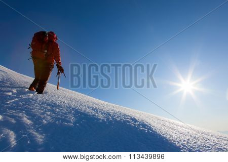 Climber walks on a glacier. Winter season, clear sky. Western italian Alps, Italy, Europe.