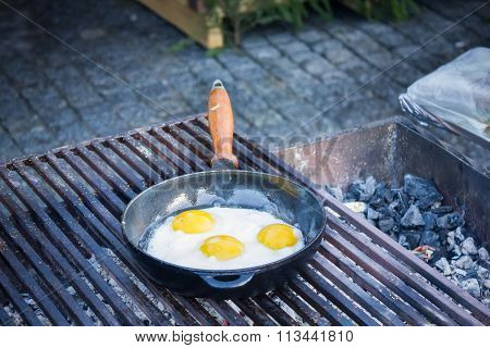 Fried eggs fried in a pan on the grill