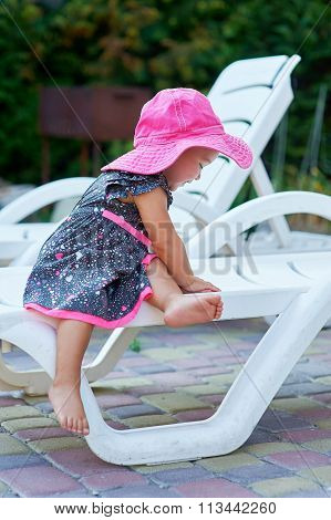 Little Girl In A Red Hat Sits On A Lounger