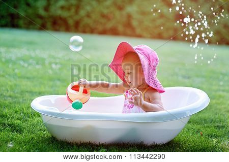 Little Girl Sitting In A Bathtub With Soap Bubbles