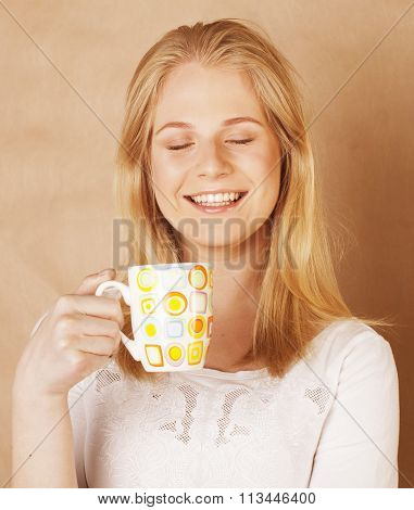 young cute blond girl drinking coffee close up on warm brown background