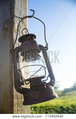Old rustic kerosene lamp hanguing from a post outdoors