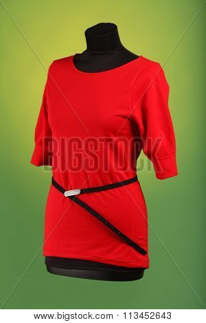 Red dress on black mannequin with black strap
