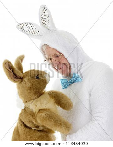 A senior man in a white rabbit outfit staring down his new competition for Easter bunny.  On a white background.