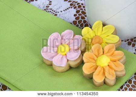 Flower sugar cookies on green napkin lace table cloth white cup