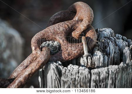 Fragment of rusty metal chain railing on old weathered wooden post in Key West harbor, Florida. Marina details.