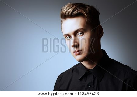 Close-up portrait of a handsome young man thoughtfully looking at the camera. Studio shot. Men's beauty, fashion.