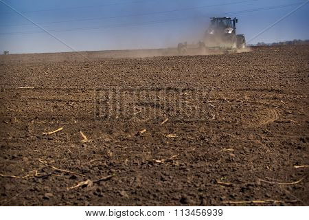 Backside Distant Cultivator Raises Great Dust On Ploughed Soil