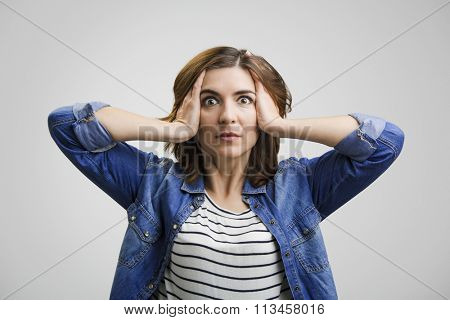 Woman holding head in hands with a astonished expression