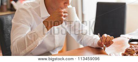 Portrait of a good looking businessman having breakfast in his kitchen