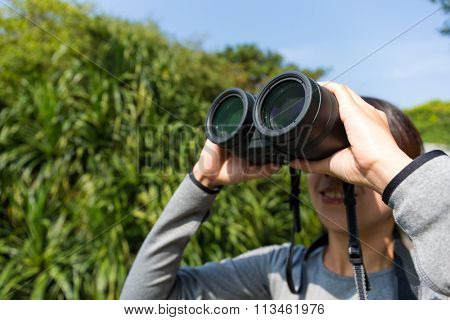 Young Woman use of the binoculars for bird watching