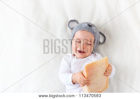 Baby boy in mouse hat lying on blanket with cheese