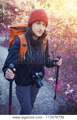 A Girl With A Camera And A Backpack.