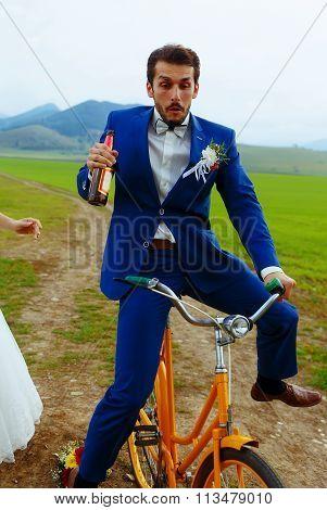 drunken groom on a bike holding a beer bottle.