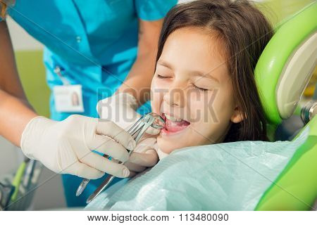 The dentist treats teeth patient, extracted tooth