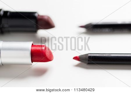 close up of two open lipsticks and lip pencils