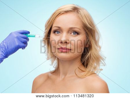 woman face and beautician hand with syringe