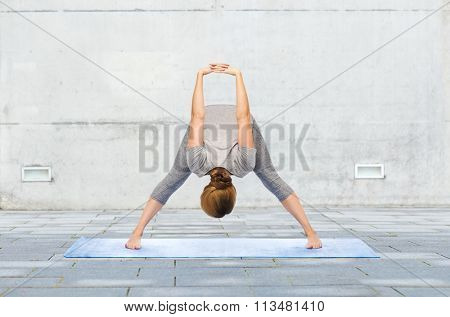 woman making yoga wide-legged forward bend on mat