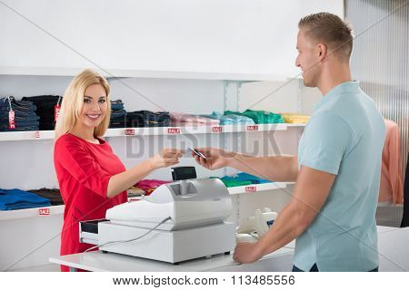 Saleswoman Receiving Payment From Male Customer