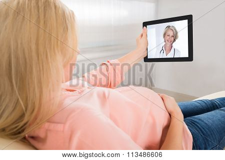 Pregnant Woman Video Conferencing With Doctor On Tablet Computer