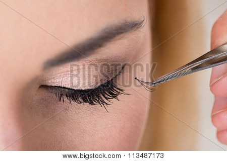 Hand Putting False Eyelashes On Woman