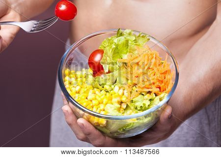 Close-up of a fit man holding a bowl of salad on grunge background