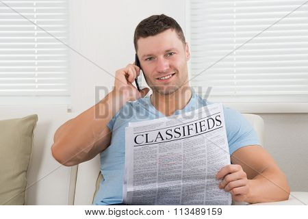 Man Reading Newspaper While Using Mobile Phone At Home