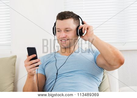 Smiling Man Listening To Music On Mobile Phone At Home