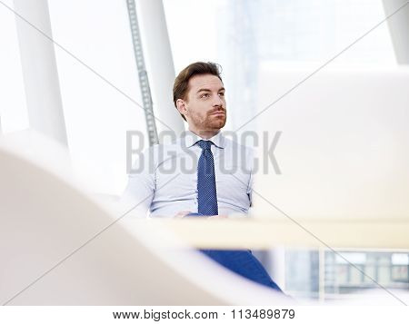Businessman Sitting At Desk Thinking