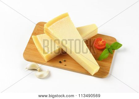 two wedges of fresh parmesan cheese and garnish on wooden cutting board