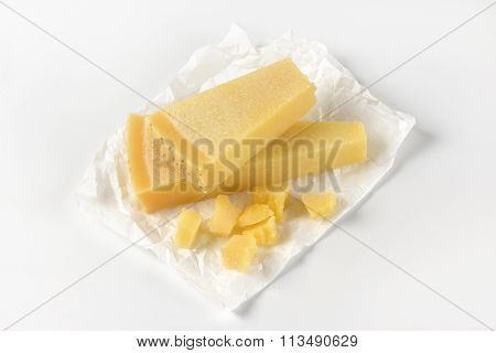 wedges and pieces of parmesan cheese on wrapping paper