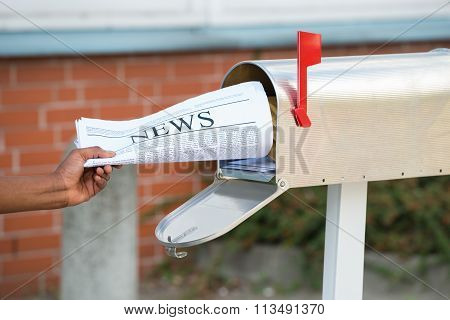 Person's Hand Opening Mailbox To Remove Newspaper