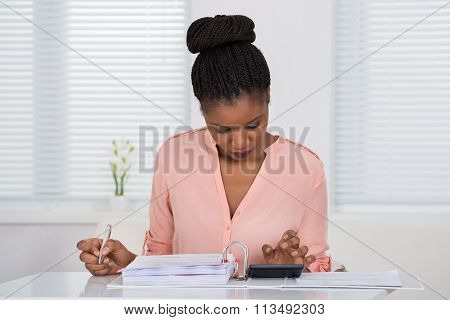 Woman Calculating Invoice With Calculator