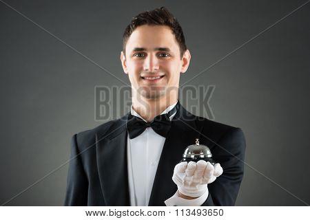 Smiling Waiter Holding Service Bell