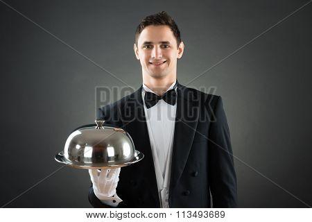 Happy Waiter Holding Tray With Cloche