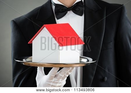 Midsection Of Waiter Holding House Model In Tray
