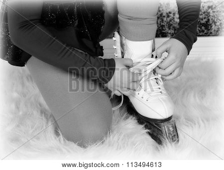 Closeup Of Young Figure Skater Tying Skates In Black And White