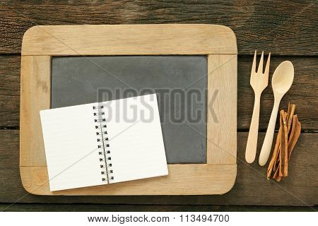 Slate chalkboard and wooden spoon and blank note book