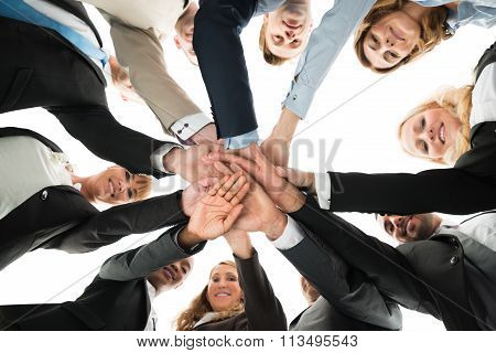 Confident Business Team Stacking Hands While Standing In Huddle