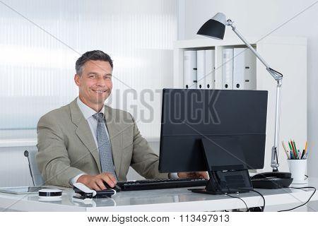 Confident Businessman Using Computer At Desk